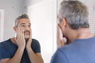 Mature man looking in bathroom mirror - ALBF00269