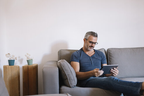 Mature man sitting on couch at home using tablet - ALBF00272