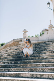 Spain, Valencia, woman sitting on stairs using smartphone - JPF00290