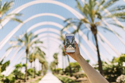 Spain, Valencia, Ciudad de las Artes y de Las Ciencias, L'Umbracle, woman taking cell phone picture at palm garden - JPF00299