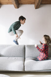 Boy jumping in the air on the couch while his sister watching him - ALBF00291