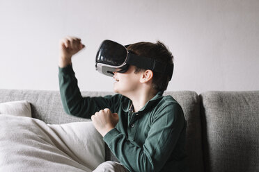 Boy sitting on the couch in the living room using Virtual Reality Glasses - ALBF00306