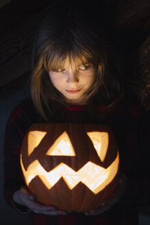 Portrait of girl with lighted Jack O'Lantern at Halloween - ALBF00312