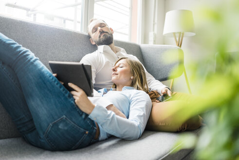 Couple relaxing on couch with tablet and cell phone - JOSF01916