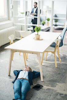 Smiling businesswoman lying on the floor in office - JOSF01919