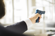 Businessman aiming with gun in office - JOSF01922