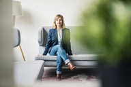 Businesswoman sitting on couch in office lounge - JOSF01925