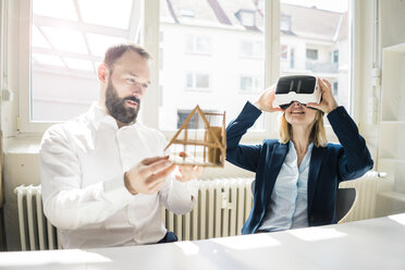 Woman and man with house model and VR glasses in office - JOSF01934