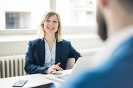 Businesswoman smiling at businessman in office - JOSF01937