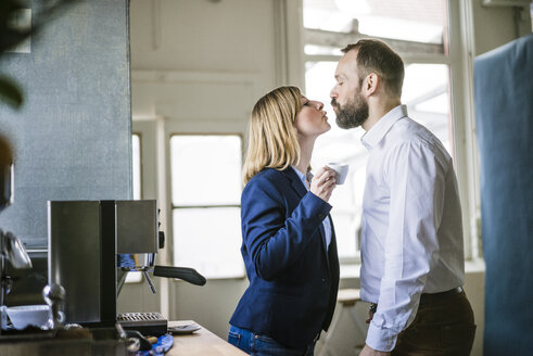Businessman kissing businesswoman in office - JOSF01940