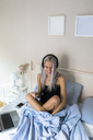 Happy young woman in bed with cell phone and headphones - GIOF03488