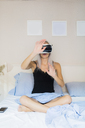 Young woman sitting in bed wearing VR glasses - GIOF03509