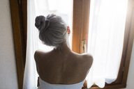 Rear view of young woman with hair bun looking out of window - GIOF03518