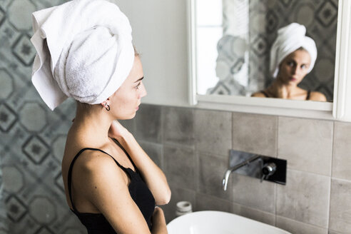 Young woman with hair wrapped in a towel looking in bathroom mirror - GIOF03521