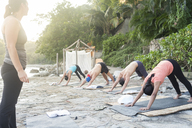 Mexico, Mismaloya, instructor with yoga class at ocean front - ABAF02183