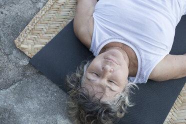 Senior woman lying on yoga mat with closed eyes - ABAF02186