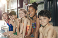 Portrait of smiling children sitting on poolside in indoor swimming pool - MFF04148