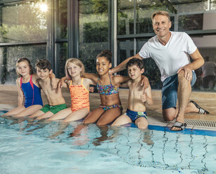 Portrait of smiling children with instructor sitting on poolside in indoor swimming pool - MFF04151