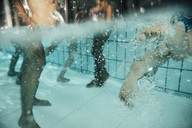 Legs of children swimming in swimming pool - MFF04157
