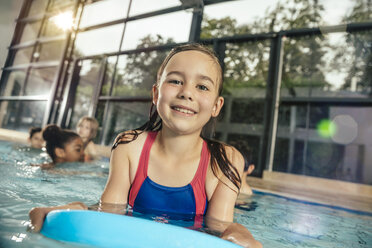 Portrait of smiling girl with friends in indoor swimming pool - MFF04160