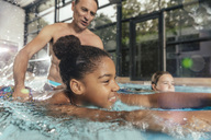 Instructor practicing with children in indoor swimming pool - MFF04163