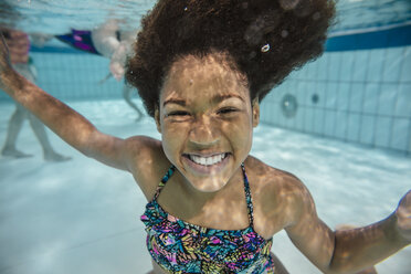 Portrait of smiling girl under water in swimming pool - MFF04166