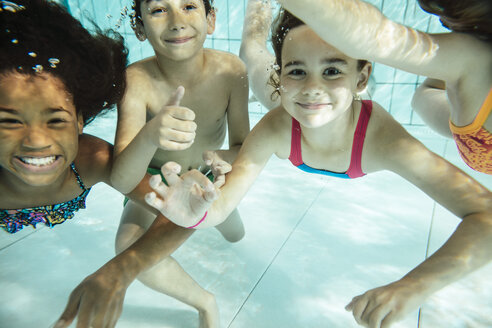 Portrait of happy children swimming under water in swimming pool - MFF04172