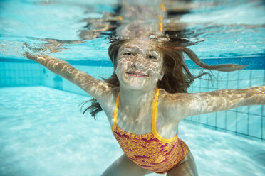 Portrait of smiling girl under water in swimming pool - MFF04175
