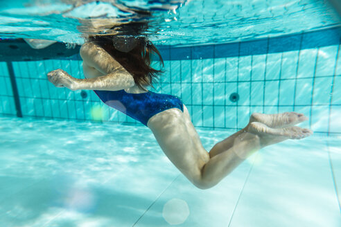 Girl swimming under water in swimming pool - MFF04178