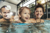 Happy parents with daughter in indoor swimming pool - MFF04184