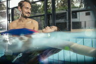 Father practicing with daughter in indoor swimming pool - MFF04196