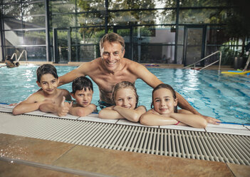 Portrait of smiling children with instructor in indoor swimming pool - MFF04205