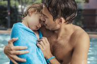 Father toweling daughter at the poolside of an indoor swimming pool - MFF04214