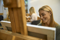 Smiling student painting on easel in art class - ZEDF01008