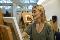 Smiling student painting on easel in art class - ZEDF01011
