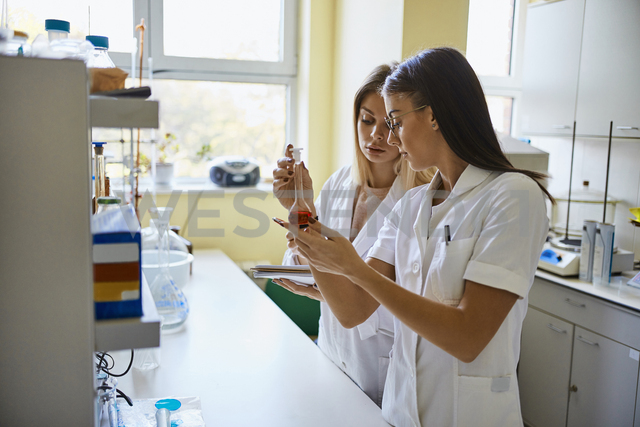 Two young women looking at liquid in flask in laboratory - ZEDF01020