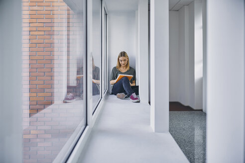 Student sitting at the window in hallway learning - ZEDF01026