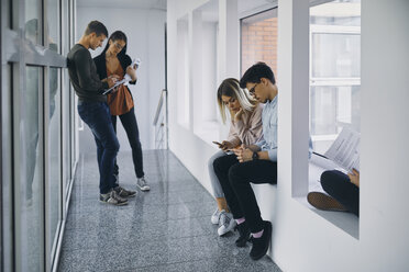 Group of students in hallway with documents and cell phones - ZEDF01029