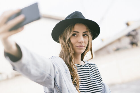Portrait of fashionable young woman wearing hat taking selfie with smartphone - GIOF03532