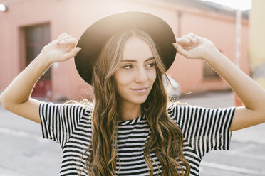 Portrait of smiling young woman wearing hat - GIOF03538