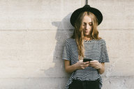 Portrait of fashionable young woman wearing hat using smartphone - GIOF03541
