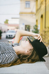 Young woman covering eyes with her hat - GIOF03544