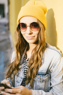 Portrait of fashionable young woman wearing yellow cap and sunglasses - GIOF03547
