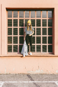 Fashionable young woman standing on window sill - GIOF03550