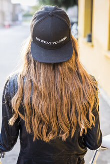 Back view of fashionable young woman wearing black baseball cap - GIOF03556