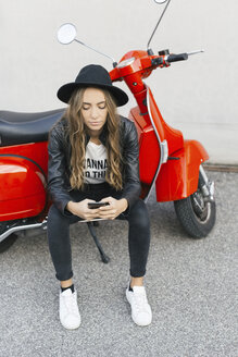 Fashionable young woman with red motor scooter using cell phone - GIOF03559