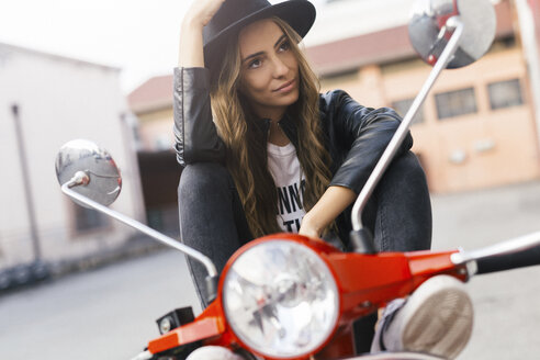 Portrait of fashionable young woman sitting on red motor scooter - GIOF03562