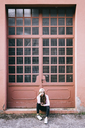 Fashionable young woman sitting in front of entrance gate - GIOF03565