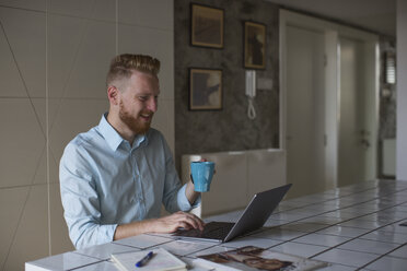 Laughing businessman with coffee mug working on his laptop at home - MOMF00300