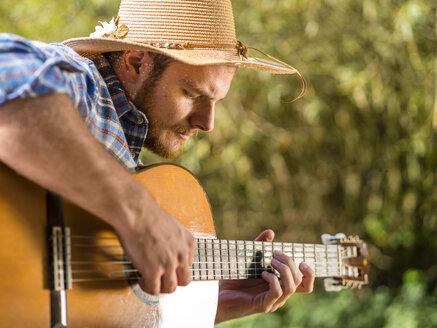 Man playing guitar in nature - STSF01435